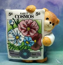Enesco Lucy and Me Lucy Rigg Bear Holding cosmos flowers seed packet