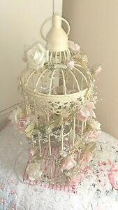Decorative shabby chic cream bird cage with rose garland and lights