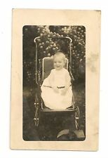 Black and White real photo postcard showing an Infant in vintage baby carriage