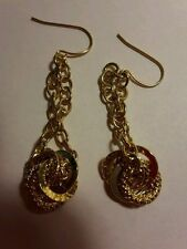 A beautiful pair of gold tone hook earrings with chain and rings.