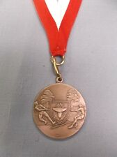 "tug of war silver medal 1 3/4"" diameter with red/white neck ribbon"