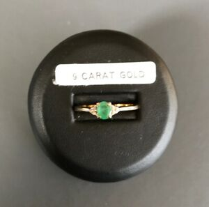 9 ct yellow gold oval emerald ring set off by small diamonds.size R