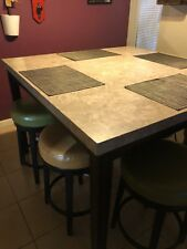 Counter high marble table with four benches. Legs are black