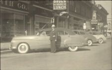 Classic Image Man in Suit 1940s Car Stores Drugs Soda Lunch Sign Where? RPPC