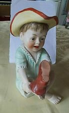ANTIQUE BISQUE PIANO BABIES - BOY IN GREEN ROMPER SUIT PULLING ON RED BOOT 6""