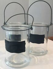 Three Clear Glass Jugs With Black Chalkboard Lables And Black Wire Handles