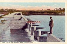 WATER FLOWING OVER RESERVOIR WEIR. COLUMBUS, NE man in suit standing on dam