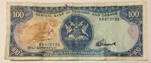 Trinidad and Tobago: $100 Dollars banknote in VG+ Condition. BR918133 TTD