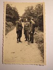 3 Soldaten in Uniform stehen auf einem Weg im Wald / Foto