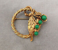 Vintage antiqued gold-tone circle pin leaves with emerald green lucite flowers