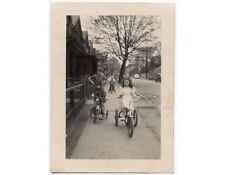 TRICYCLES - CHILDREN RIDING 3 TRIKES ON BUSY SIDEWALK PHOTO