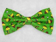 (1) PRE-TIED BOW TIE - CAMP PEANUTS - WOODSTOCK ON A GREEN BACKGROUND