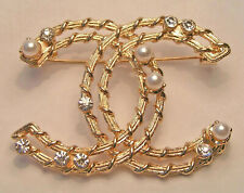 clear crystals brooch . Gold colour metal,faux white pearlsand