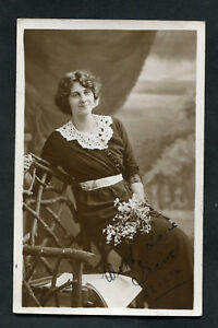 Dated 1914: Photo Card: Young Lady Holding Flowers in a Dress Posing in a Chair