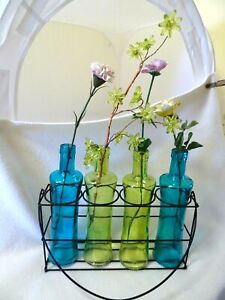 COLLECTION OF 4 COLORED GLASS BOTTLES WITH BLACK METAL HOLDER W. HANDLE-INSIDE/O