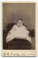 CABINET CARD BABY WITH SERIOUS EXPRESSION SEATED ON VELVET CHAIR. TIDIOUTE, PA.