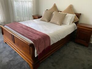 Solid mahogany sleigh bed and matching bedside tables.
