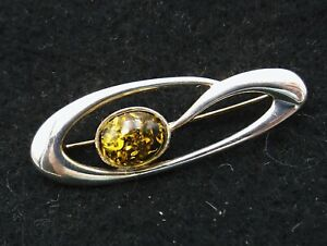 Sterling silver brooch curve shaped design with a faux green amber stone