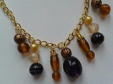 Gold colour chain necklace. Amber, bronze and black beads, drop pendant. BY