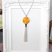 Long silver necklace with mustard yellow focal bead and tassel pendant