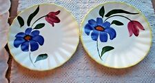 2 WHITE SAUCERS WITH A BLUE & RED FLOWER & YELLOW TRIM