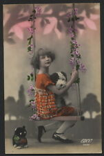 MB2262 LITTTLE GIRL WITH HER TOYS ON A FLOWERSWING RPPC HAND. COL