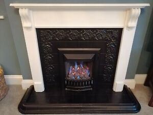Gas fire with tiled back & hearth and white wooden surround.