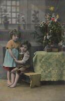 Postcard Merry Christmas Little Girls Hugging Next to Christmas Tree