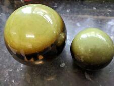 Two green/bronze coloured ceramic decorative spheres 12cm and 8cm diameter