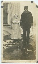 Tall Man Short Woman Stand by a Home - Some Snow on ground - American Culture
