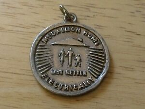 VINTAGE MEDALLION HOME LIVE BETTER ELECTRICALLY BRASS SILVER TONE, BILINGUAL