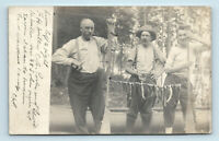 1910 VIEW OF MEN w/ FISH CATCH HUNG ON OARS - ICONIC FISHING - VTG RPPC PHOTO