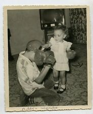 1950s  snapshot Photo  Girl with boxing gloves hits young boy  TV set television