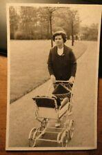 Frau mit Kinderwagen beim Spaziergang / Foto