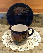 AN UNMARKED COBALT BLUE EARTHENWARE TEA CUP & SAUCER SET WITH GOLD TRIM