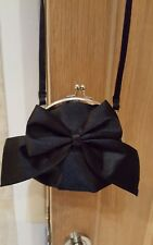 Girls black bag with black bow and a silver kisslock clasp from New Look. Worn