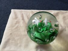 THIS IS A LOVELY GLASS PAPERWEIGHT. IT HAS TWO BIRDS FLYING OVER GREEN GRASS