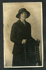C1920s Photo Card: Lady in Hat & Coat Standing By A Chair