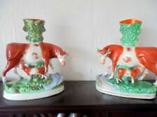 A PAIR OF VICTORIAN STAFFORDSHIRE COW VASES