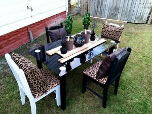 This is a black glass dining room set with four chairs cheetah print fabric