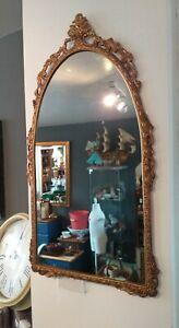 Vintage look Gilt gold metal Mirror with ornate decorative frame.