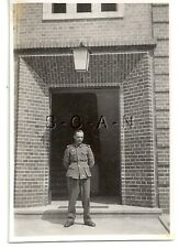 WWII German RP- Army Soldier- Uniform- Stands in Front of Brick Barracks- Lamp