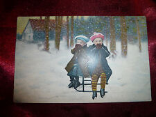 Antique POSTCARD Children dressed up warm, on a sledge in snow 1900s