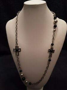 Long necklace with crosses and beads, a little goth in appearance, earrings