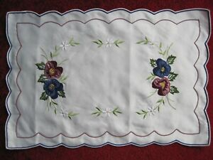 """A PLACEMAT  18"""" x 12"""",  PANSIES EMBRODERED DESIGN ON IVORY SATIN LIKE MATERIAL."""
