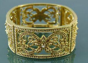 Gold bangle bracelet in a smokey grey crystal set flower design