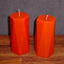 Pair of orange hexagon shaped pillar candles.