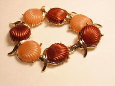 Gold colored fashion bracelet accented with copper and pinkish colored shells