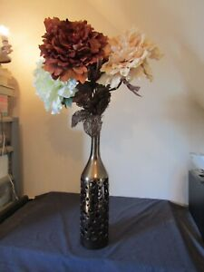 TALL FLOOR VASE IN BRONZE COLOURED CERAMIC WITH FLOWERS.