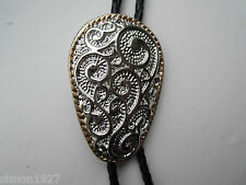 Bolo tie silver scrolled pattern gold surround.